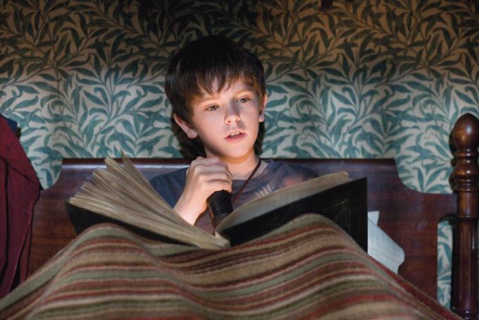 Bild zu Junge liest mit Taschenlampe im Bett