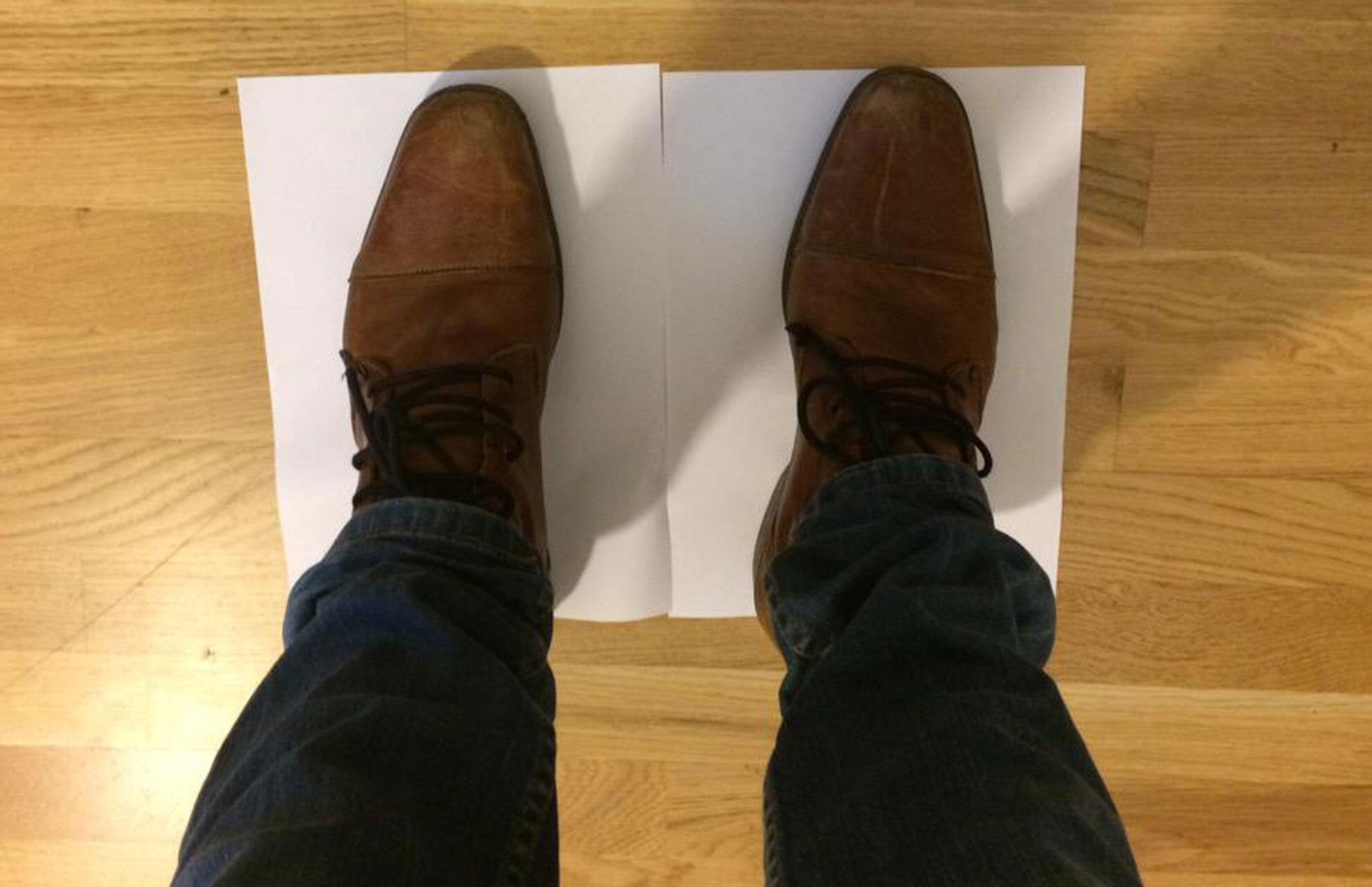 Bild zu Mann steht auf zwei Blatt Papier