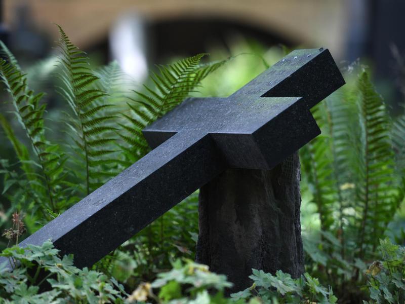 Bild zu Steinkreuz liegt auf einem Grab