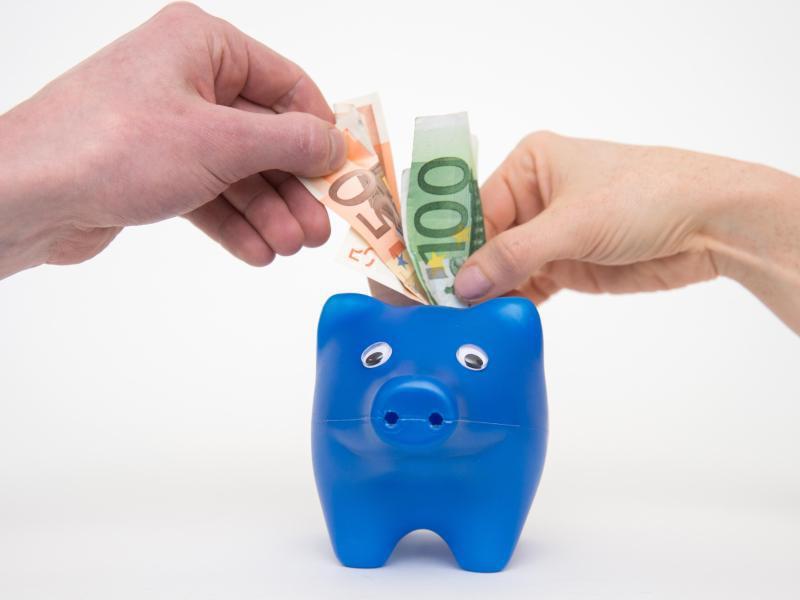 Bild zu Zwei Hände strecken Geld ins Sparschwein