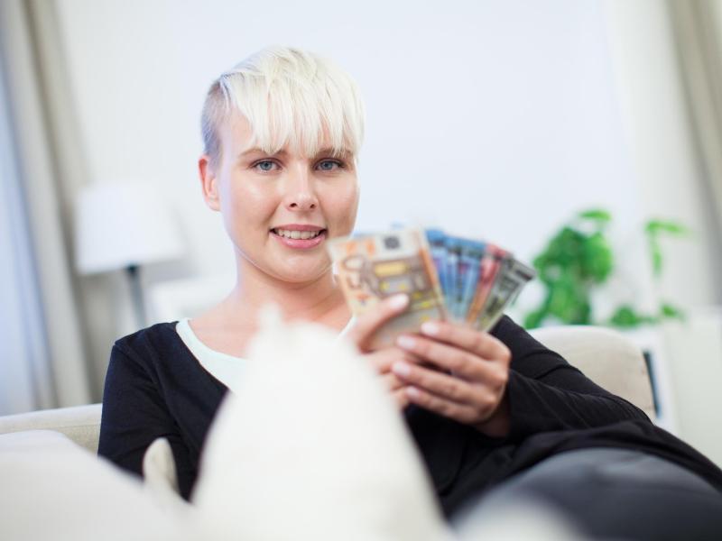 Bild zu Eine Frau mit Geldscheinen in den Händen
