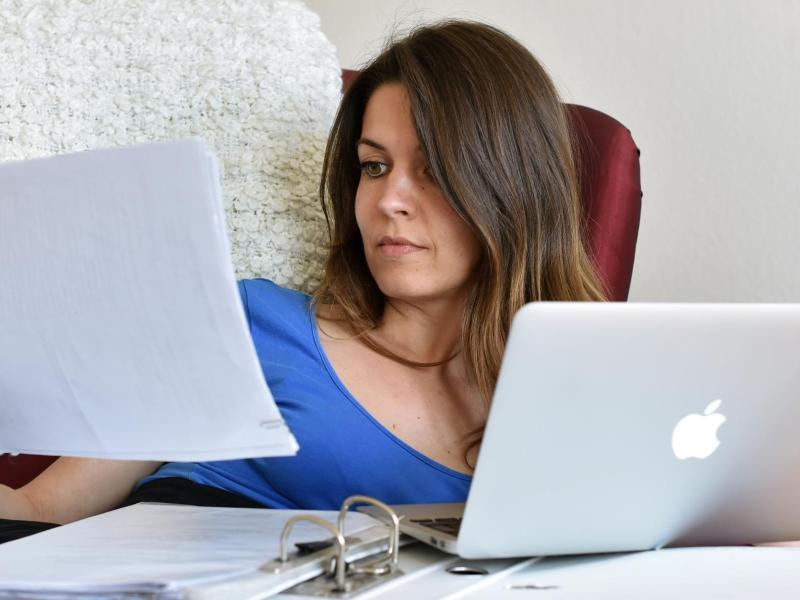 Bild zu Frau mit Unterlagen und Laptop